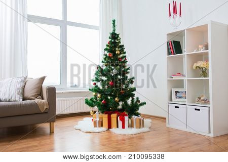 holidays and interior concept - artificial christmas tree and presents at home living room