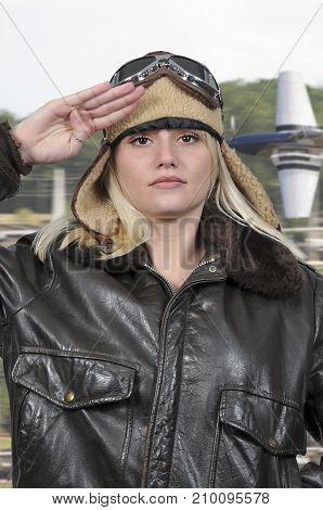 Woman pilot wearing vintage pilot helmet flight jacket and goggles