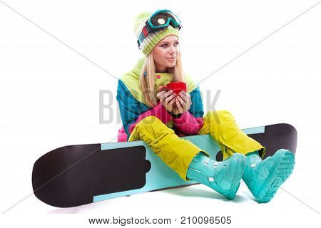 Attractive Young Woman In Ski Suit And Ski Glasses Sit On Snowboard, Hold Red Cup