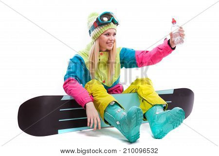 Pretty Woman In Ski Costume With Bottle Of Water Sit On Snowboard
