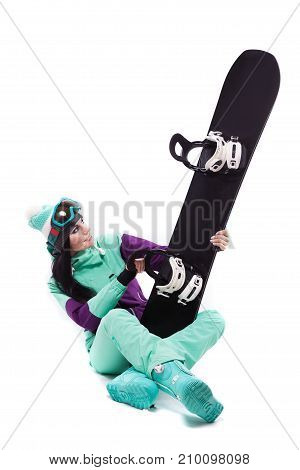 Young Pretty Woman In Purple Ski Costume And Ski Glasses Hold Black Snowboard