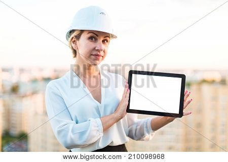 Pretty Young Forewoman In Helmet Stand On The Roof And Show Empty Tablet