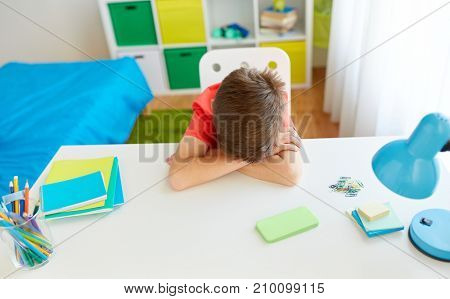 cyberbullying, technology and people concept - tired or sad student boy with smartphone lying on desk at home suffering from bullying