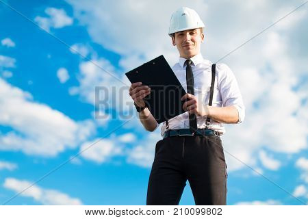 Young Attractive Foreman In White Helmet, Tie And Braces Stand On The Roof With Tablet