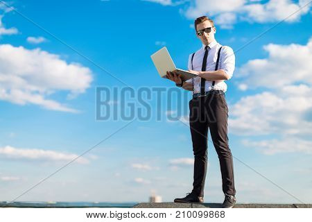Young Serious Busunessman In White Shirt, Tie, Braces And Sunglasses On The Roof With Laptop
