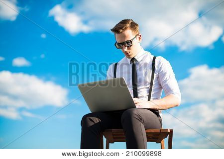Attractive Serious Busunessman In White Shirt, Tie, Braces And Sunglasses Work With Laptop On The Ro