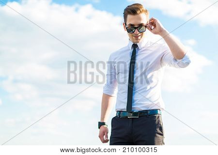 Serious Young Busunessman In White Shirt, Tie And Sunglasses Stand On The Roof