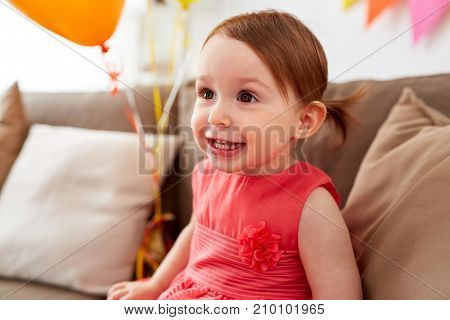 childhood, holidays, emotions and people concept - happy baby girl on birthday party at home