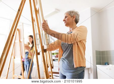 art school, creativity and people concept - happy senior woman artist with easel drawing at studio