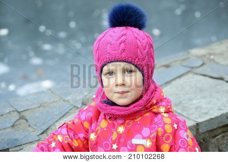 Portrait of cute little caucasian girl in a beautiful knitted pink hat with large fur pompon having fun in a forest or city park in winter.