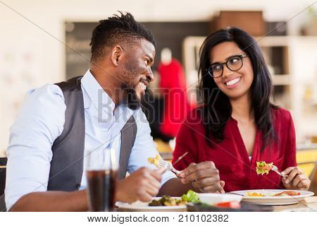 leisure, food and people concept - happy couple eating at restaurant
