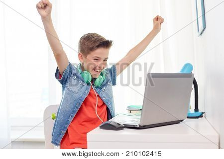 technology, gaming and people concept - boy with headphones playing video game on laptop computer and celebrating victory at home