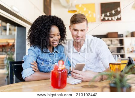 leisure, technology and people concept - happy man and woman with smartphone and beer at bar or restaurant