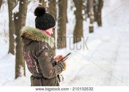Beautiful Caucasian Girl In Sport Jacket With Fur Collar And Knitted Hat Looking At The Display Of C