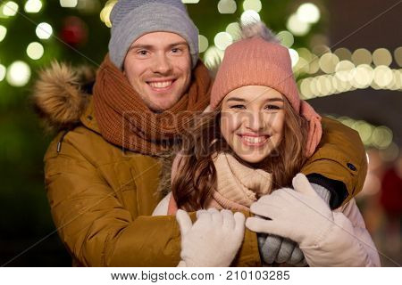 winter holidays and people concept - happy young couple dating and hugging at christmas tree in evening