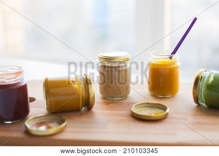 baby food, healthy eating and nutrition concept - vegetable or fruit puree or baby food in glass jars and feeding spoon on wooden board