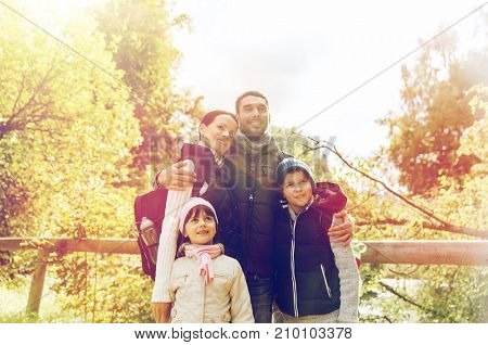 travel, tourism and hike people concept - happy family walking with backpacks outdoors
