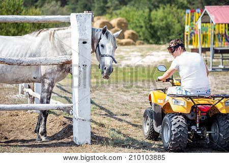 Caucasian Man On Atv Quad Bike Meet Beautiful White Horse On A Farm Or Ranch. Evolution Of Vehicles