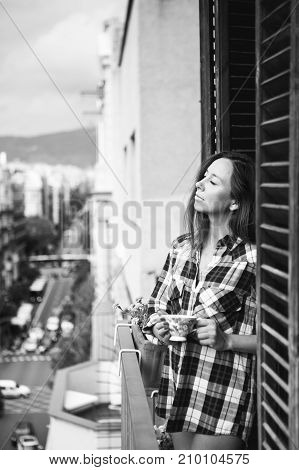 Beautiful young woman relaxing on balcony with city view holding cup of coffee or tea. Black and white vertical photo.