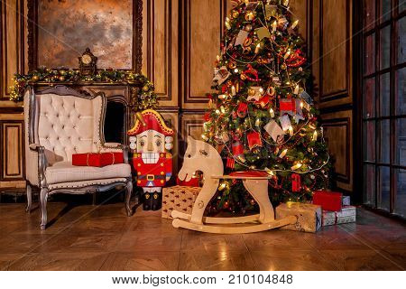 Christmas decoration in grunge room interior with fireplace, horse rocking kids chair, classic new year tree with presents