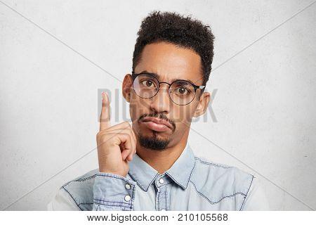 That Is! Serious Dark Skinned Man Raises Fore Finger As Gets Brilliant Or Grandiose Idea, Poses Agai