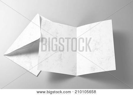 Blank greeting card and envelope over grey background