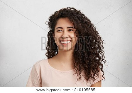 Beautiful Female With Curly Bushy Hair, Mixed Nationality, Dressed Casually, Smiles Broadly, Shows W