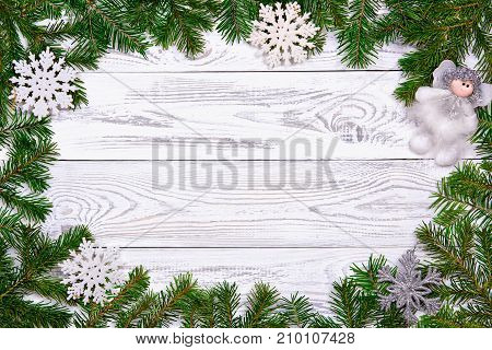 Christmas fir tree with decoration on dark wooden board.