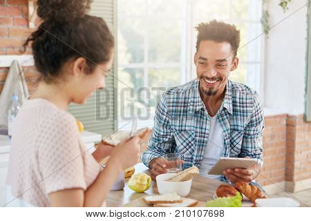 Indoor Shot Of Happy Bearded Man With Specific Appearance, Uses Tablet Computer For Searching Social