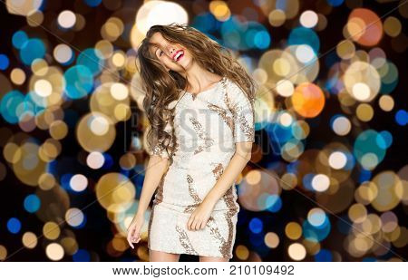 holidays, hairstyle and people concept - happy young woman or teen girl in fancy dress dancing over festive lights background
