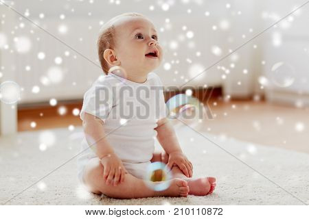 childhood, babyhood and people concept - happy little baby boy or girl sitting on floor with soap bubbles around at home over snow
