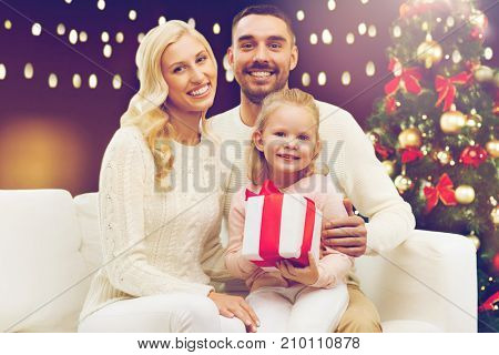 family, christmas, holidays and people concept - happy mother, father and little daughter with gift box sitting on sofa over lights background