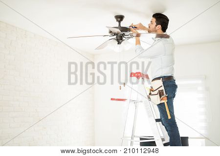 Electrician Fixing A Ceiling Fan