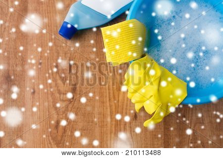 housework, housekeeping and household concept - basin with cleaning stuff on wooden background over snow