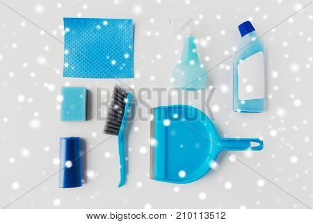 housework, housekeeping and household concept - cleaning stuff on white background over snow