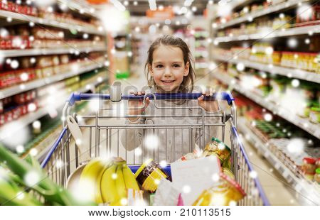 sale, consumerism and people concept - happy little girl with food in shopping cart at grocery store or supermarket over snow