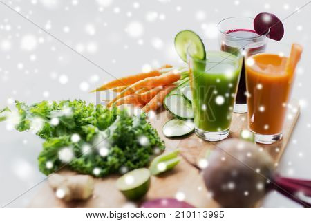 healthy eating, drinks, diet and detox concept - glasses with vegetable fresh juices and food on table over snow