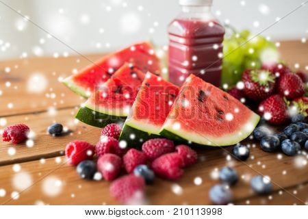 healthy eating, food, diet and vegetarian concept - watermelon slices, bottle of fruit juice or smoothie and berries on wooden table over snow