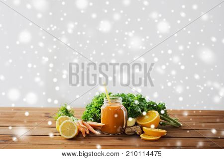 healthy eating, food, diet and vegetarian concept - glass jug of carrot juice, fruits and vegetables on wooden table over snow