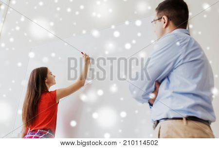 education, school, learning and people concept - student girl writing something on blank white board and teacher in classroom over snow