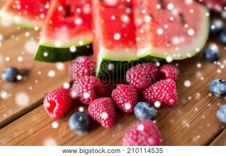 healthy eating, food and vegetarian concept - close up of raspberry, blackberry and watermelon slices on wooden table over snow