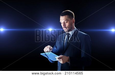 business, people and future technology concept - businessman in suit working with transparent tablet pc computer  with laser lights over black background