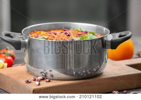 Saucepan with delicious chili con carne on wooden board