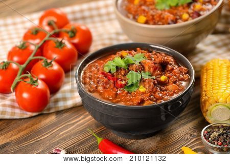 Bowl with delicious chili con carne on table