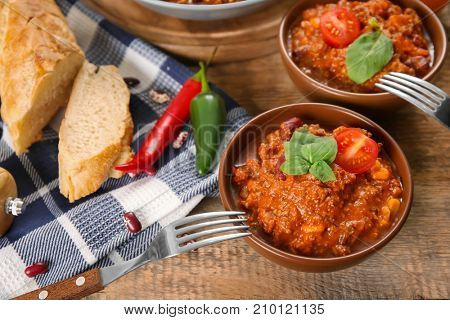Bowls with delicious chili con carne on table