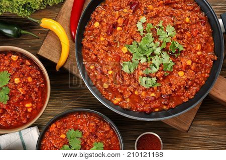 Bowls and frying pan with delicious chili con carne on table