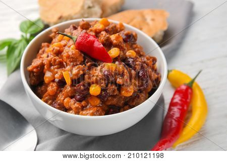Composition with delicious chili con carne in bowl on table