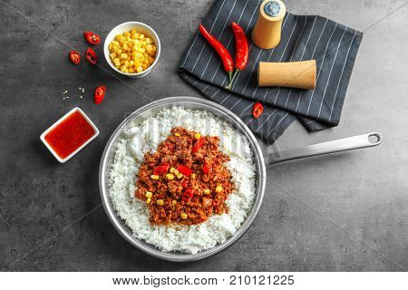 Saucepan with chili con carne and rice on dark background
