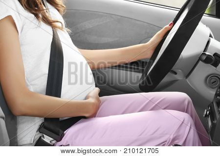 Pregnant young woman driving car