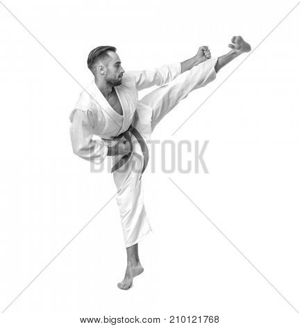 Young man practising karate on white background